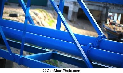 Industrial blue pipelines next to bridge above river. Video...