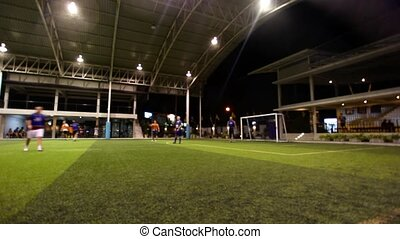 THAILAND, KOH SAMUI, FEBRUARY 2, 2014: men playing soccer on the sports field at night with lighting field. Video time lapse speed up