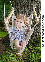 Little cute baby boy riding on hammock swing at park -...