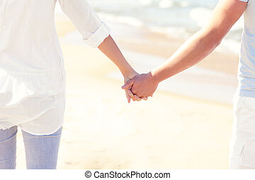 Couple holding hands at the beach