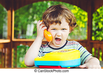 Little child talking on a toy phone