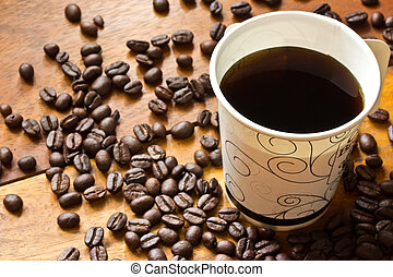 a paper cup of black coffee and coffee beans on wooden table