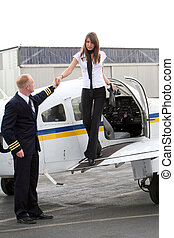 Pilot and young woman get out of the private plane - A pilot...
