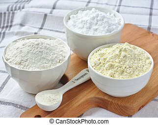 Three bowls with gluten free flour - rice flour, millet...