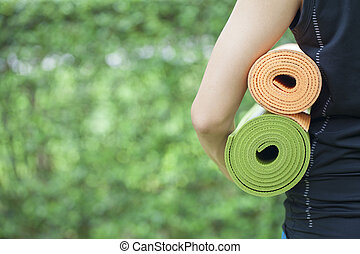 Young woman holding yoga mats - A young woman is holding...