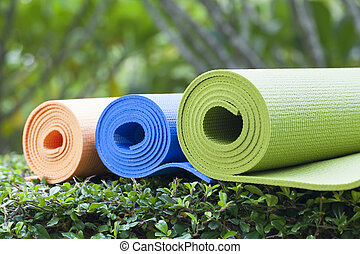 yoga mats - The colorful yoga mats are set on the grass