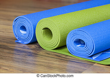 yoga mats - The colorful yoga mats are set on the floor