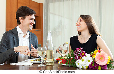 Man and woman having romantic dinner - Young man and smiling...