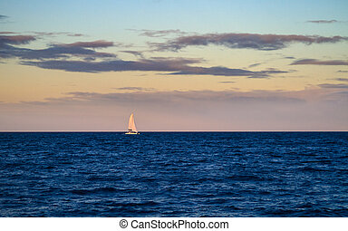Luxury Yacht Sailing at Dusk - A luxury sailboat sailing on...