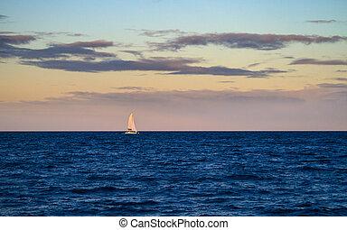 Luxury Yacht Sailing at Dusk - A luxury sailboat sailing on...