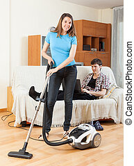 Smile woman cleaning with vaccuumcleaner at home while young...
