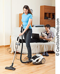 Girl cleaning at home while man with cat resting over sofa
