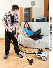 man cleaning while girl lying with notebook - Young man...