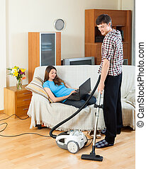 Man doing house cleaning with vaccuum cleaner while girl...