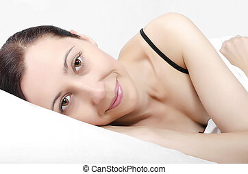 Woman lying on bed - Smiling woman lying on her bed in the...
