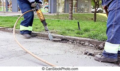 Works on the road - Worker with a shovel collects broken...