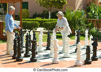 Senior couple playing chess at the resort during vacation