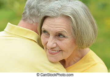 Happy elderly couple at nature on leaves background