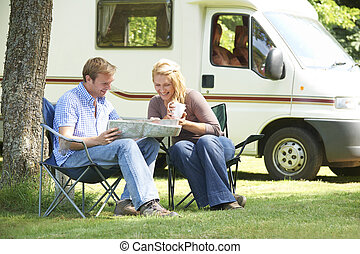 Couple Relaxing Outside Motor Home On Vacation