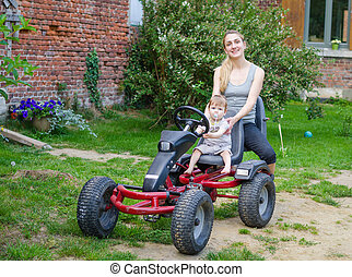 Little cute boy driving pedal car with young mother - Little...