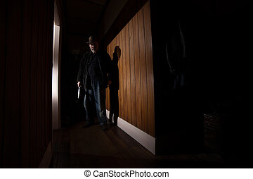 Creepy Intruder - A creepy intruder in a cowboy hat holds a...
