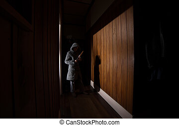 Creepy Girl Intruder - A creepy girl in a hooded coat holds...
