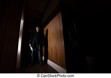 Creepy Intruder - A creepy intruder holds a mean looking...