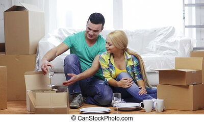 smiling couple unpacking boxes with kitchenware