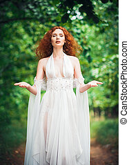 Gorgeous red-haired woman wearing white dress in a garden -...
