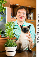 Portrait of elderly woman with flowers and cat