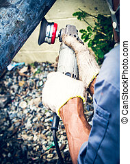 electric polisher - Man using hold electric polisher on pole...