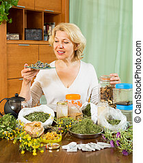 Mature woman with herbs at table - Smiling aged woman...