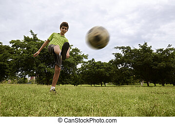 Kid playing football and soccer game in park