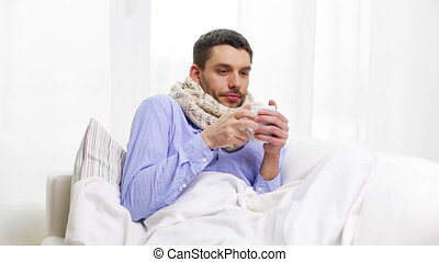 ill man with flu drinking hot tea at home