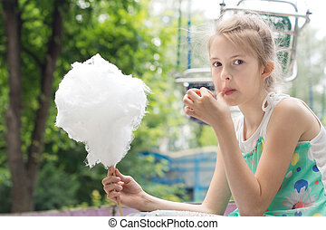 Pretty young girl eating a stick of candy floss picking at...