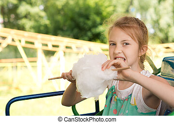 Happy young girl eating candy floss at the fair as she sits...
