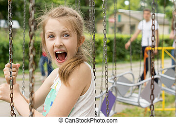 Excited little girl on a ride at the fairground screaming in...