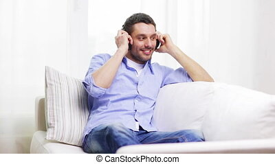 smiling young man with headphones at home - technology,...