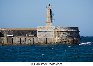 Stone Lighthouse over ocean and blue sky - Old small stone...