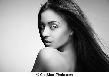 Attractive smiling woman with long hair on grey - Portrait...