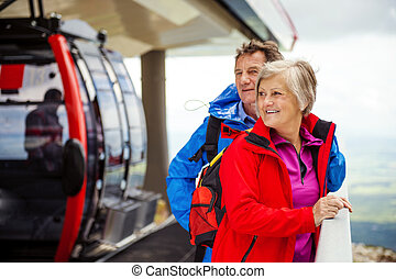 Senior hikers waiting for cableway - Senior hikers couple is...