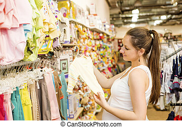 Pregnant woman shopping - Young pregnant woman choosing baby...