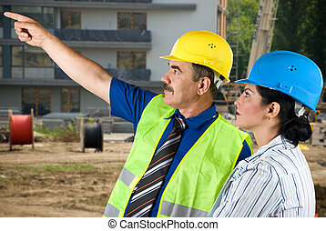 Architect team on site pointing - Two architects mature man...