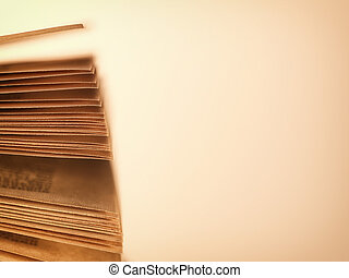 Scattered pages of an open book, on beige