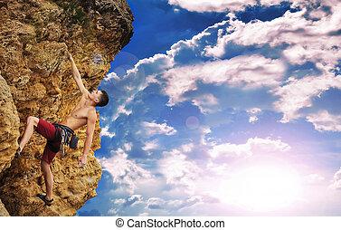 Climber and sunset - Muscular man climbing on rock at sunset