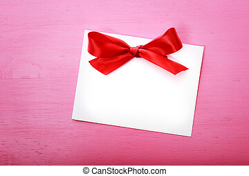 Blank message card on pink wooden board