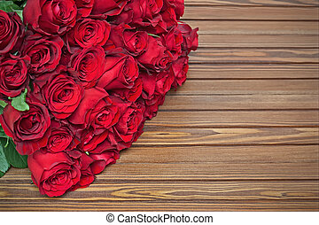 Colorful flower bouquet from red roses on wooden background....