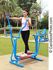 woman exercising with exercise equipment in the park - woman...