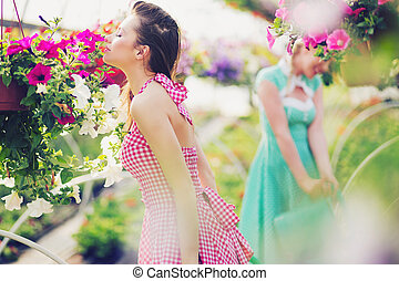 Two sexy ladies smelling the flowers