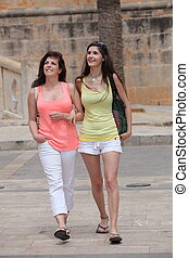 Two beautiful young women strolling in town in casual summer...